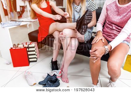 Cropped image of teen girls sitting on bench relaxing after shopping in clothing store. Young stylish woman tying up new sneakers putting her leg on her friend s lap.