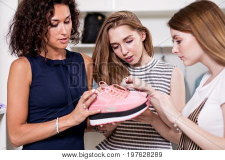 Three young girlfriends examining holding new pair of sports footwear standing in fashion showroom.