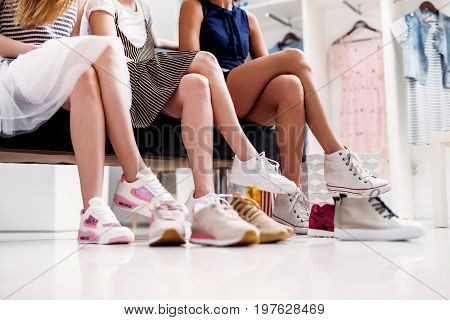 Close-up shot of young women trying on different footwear while sitting in a shoe store.