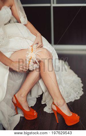 The bride in orange sandals puts on a garter