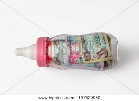 UAE dirham assorted notes in a feeding bottle. Stock image. 'Young economy' - creative concept.
