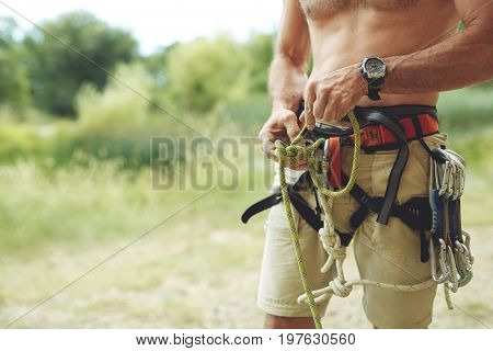 A man climber Knots a knot on a climbing harness. hands in chalk close up