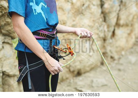 woman belaying other climber through a belay device. Tubular device on locking carabiner. hands and belay device close up