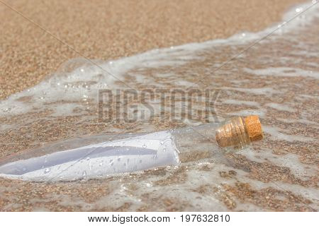 Paper Message in a glass bottle with a cork on the sand. In the background the sea and waves. A note on salvation please help