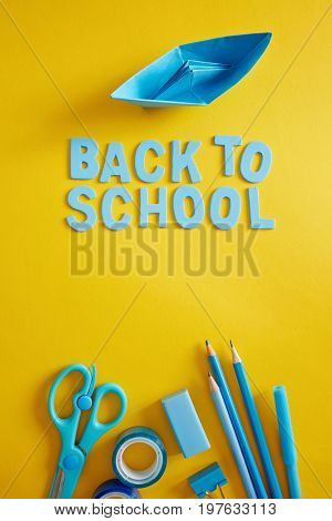 Back to school supplies and letters on yellow background.