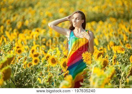 On the yellow field of sunflowers stands a young woman a summer bright day.