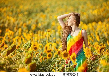 Girl on a yellow field of sunflowers in a summer sunny day.