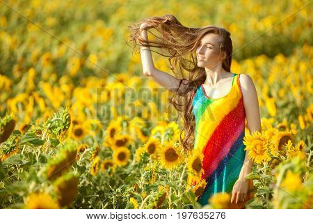 Woman with long hair is standing in the field among sunflowers.