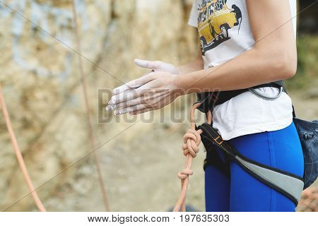 woman climber is preparing to climb on the rock. climbing harness with rope and hands in chalk close up