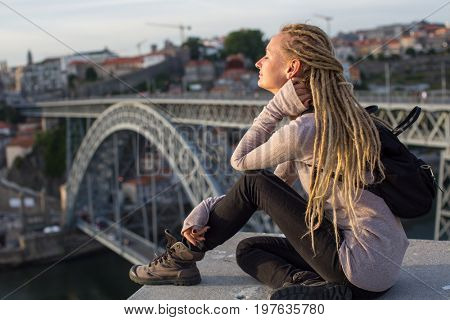 Young beautiful blonde sitting opposite the Dom Luis I bridge across the Douro river in Porto, Portugal.
