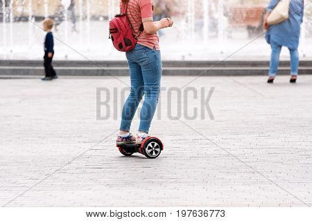 Young woman riding a hoverboard on the city square. New movement and transport technologies. Close up of dual wheel self balancing electric skateboard. People on electrical scooter outdoors