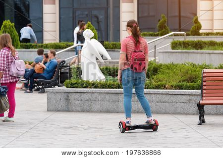 Young woman riding a hoverboard on the city square. New movement and transport technologies. Dual wheel self balancing electric skateboard. People on electrical scooter outdoors