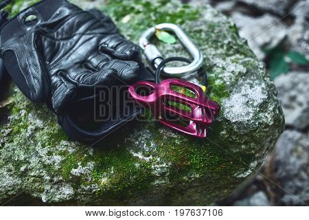 climbing equipment on the old stone with moss. climbing belaying device and carabine and black leather gloves