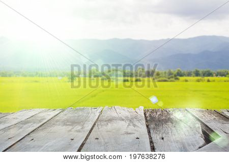 perspective old wooden board empty table in front of blurred background of rice field landscape lens flare can be used for display or montage your products. Mock up for displaying product.