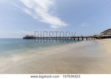 Malibu Pier beach with motion blur water in Los Angeles County, California.