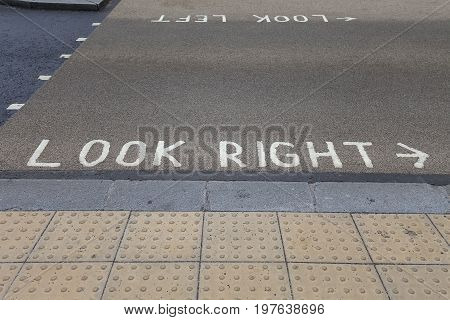 Pedestrian crossing left side traffic instruction : look right and look left painted on the street London United Kingdom