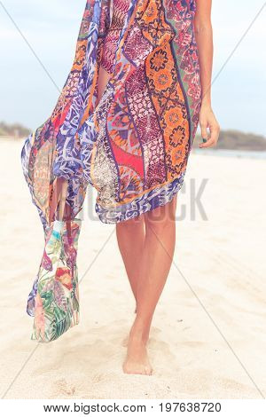 Woman tourist walking on a tropical summer vacation beach wearing sunglasses and beach bag relaxing on travel holidays. Young lady in luxury fashion beachwear, Bali island.