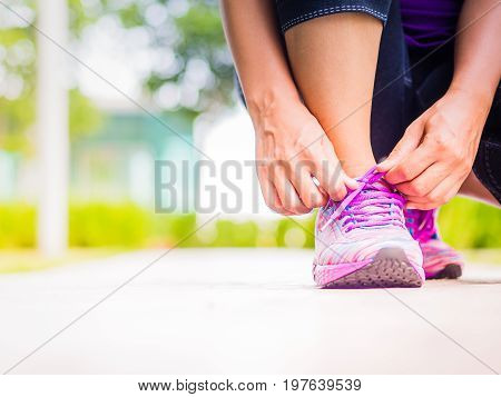 Running shoes - closeup of woman tying shoe laces. Female sport fitness runner getting ready for jogging in garden backgroound