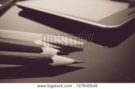 Tablet and pencil on office desk, black abd white effect.technology or education background.