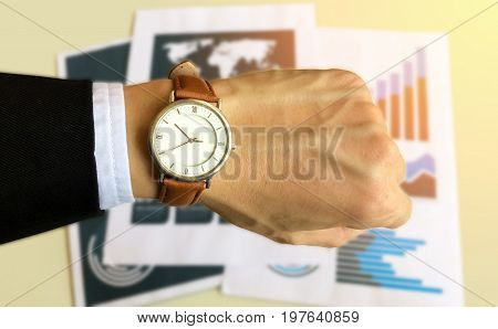 Watch on the left hand of business man  with data report background for business and financial concept.