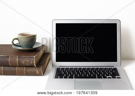 Cropped shot of open laptop computer two books and mug of coffee or tea resting on white desk. Technology communication job occupation and leisure concept. Freelancer's workplace. Mock up