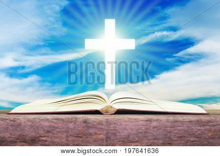 Open holy bible with white cross in the blue sky back ground.
