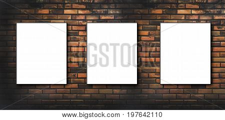 Three blank, white canvas frames hang on brick wall.Three blank billboards attached to a buildings exterior brick wall.