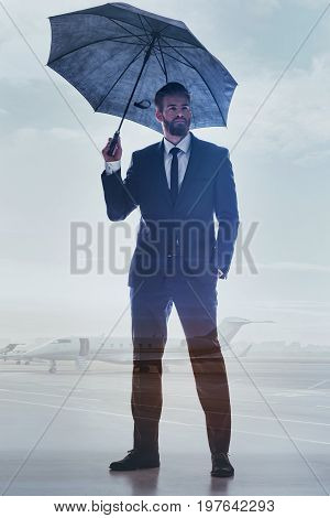 Ready for flight in the successful future. Full length portrait of confident businessman standing on the abstract airport with umbrella under his head. Planes on background. Double exposure