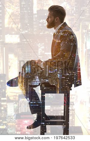 Being on the top of urban business. Profile of pensive bearded man sitting on high stool and thinking about his job. Urban scene with skyscrapers lights creating double exposure