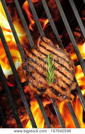 Grilled pork steak on the flaming grill