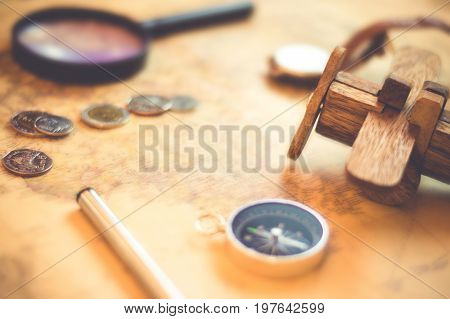 Compass on vintage world map with coins, pen, wrist watch, plane and Magnifying glass for vacation and travel concept, selective focus.