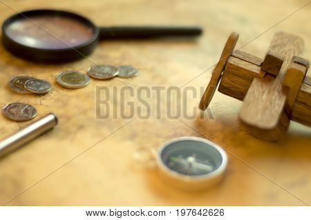 Compass on vintage world map with coins, pen, wrist watch, plane and Magnifying glass for vacation and travel concept, selective focus