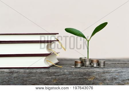 Coins stack with growing tree and book stack , Money, Financial, Business Growth concept.selective focus.