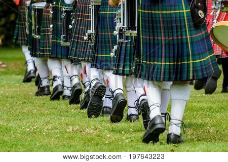 Photo of men below waist in green kilts and white socks are marching in New Zealand