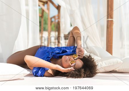 Happy youthful mulatto woman is lying on large sunbed with roof, curtains and pillows. She is looking upwards through sunglasses, holding them by hands