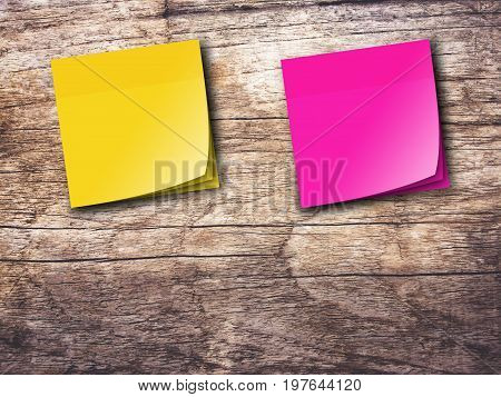 Yellow and pink reminder sticky note on wooden wall background,empty space for text.