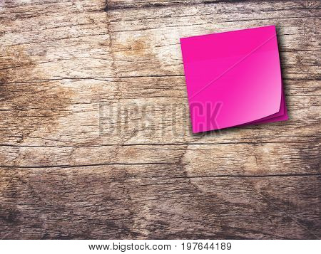 Pink reminder sticky note on wooden wall background,empty space for text.