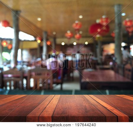 Empty brown wooden table surface and restaurant interior with some people meeting blur background with bokeh image, for product display montage,can be used for montage or display your products.