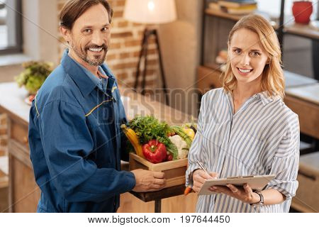 Simple and convenient. Busy delighted nice lady signing some papers and confirming the receiving of vegetables while thanking the courier