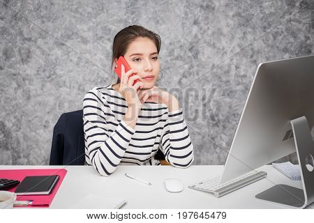 Beautiful young woman looking at a computer screen and thinking at the office stressed and nervous