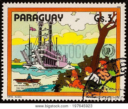 Moscow Russia - July 30 2017: A stamp printed in Paraguay shows Finn Friends and Riverboat on Mississippi Adventures of Tom Sawyer by Mark Twain series