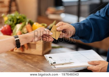 No cash needed. Intelligent enthusiastic wonderful woman receiving a package from the store and not using cash while compensating the expanses for delivery