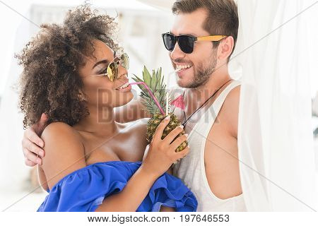 Portrait of happy young bearded guy and mulatto girl in sunglasses hugging and drinking juice from fresh pineapple together. They are playfully looking at each other with adoration smile