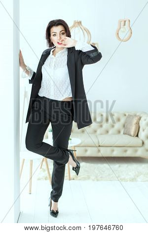 Charismatic woman dances near the wall. She is dressed in a business suit.