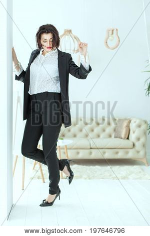 Young and charismatic woman dances near the wall on it is a stylish business suit.