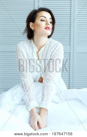 Beautiful woman sitting in bed in the early morning.