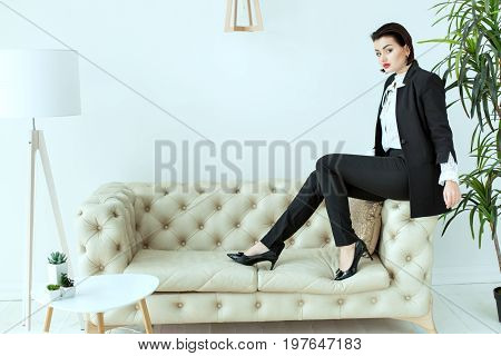 Beautiful business woman is sitting on a sofa in shoes.