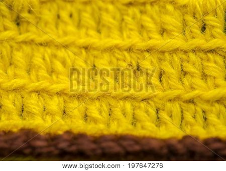A beautiful closeup of a hand made crochet pattern of a colorful wool yarn. Soft and warm natural sheep wool. Pattern of wool.