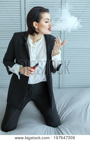 Cute woman smoking e-cigarette with smoke in the room.
