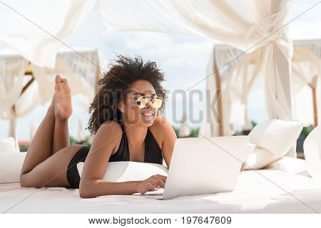 Portrait of cheery youthful mulatto woman lying on luxury lounger and typing something on notebook. She is looking happily at screen through reflex sunglasses and smiling